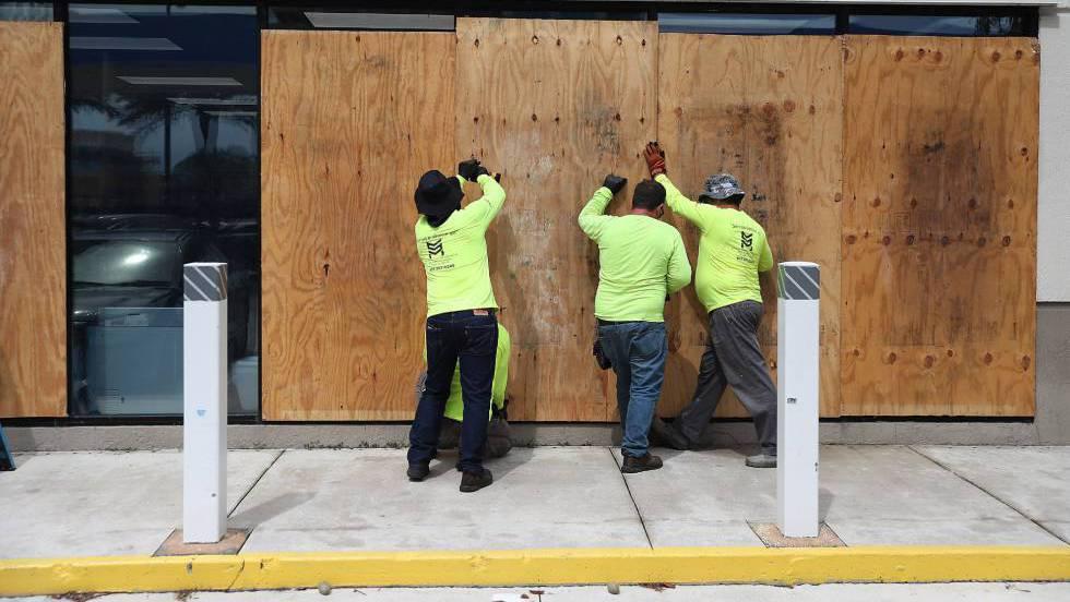 trabajadores cubren ventanales miami por huracan dorian