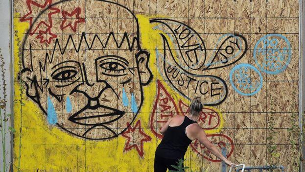 manifestante pintando un mural