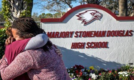 mujeres se abrazan frente a monumento en Parkland