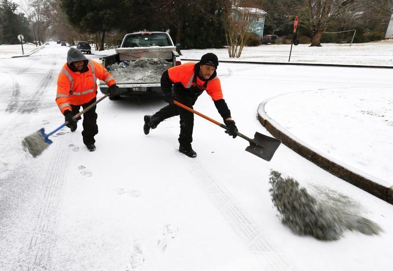 trabajadores echan sal y arena sobre la nieve